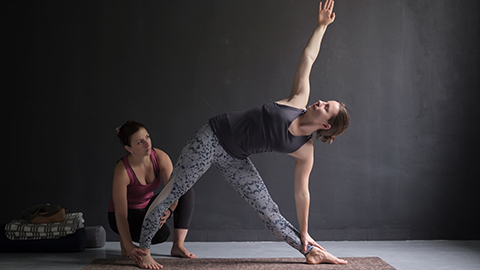 A woman performing an assisted yoga stretch