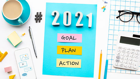 Goal, Plan, Action on a board surrounded by an array of office supplies