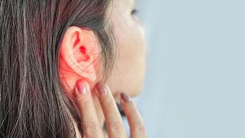 Woman touching a painful ear that is glowing red