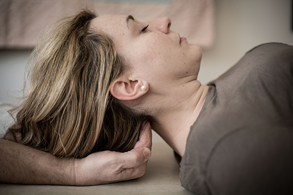 A woman lying on her back receiving craniosacral therapy