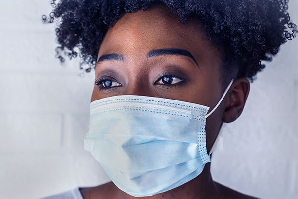 A woman wearing a blue surgical mask