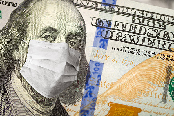 One hundred dollar bill with a surgical mask over Benjamin Franklin's face