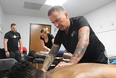 Cortiva Institute Graduates Marc Marlowe and Amy Eberbach perform massage on two Phoenix Rising players