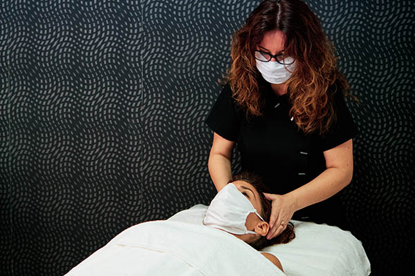 Massage therapist wearing face mask giving massage to client wearing face mask