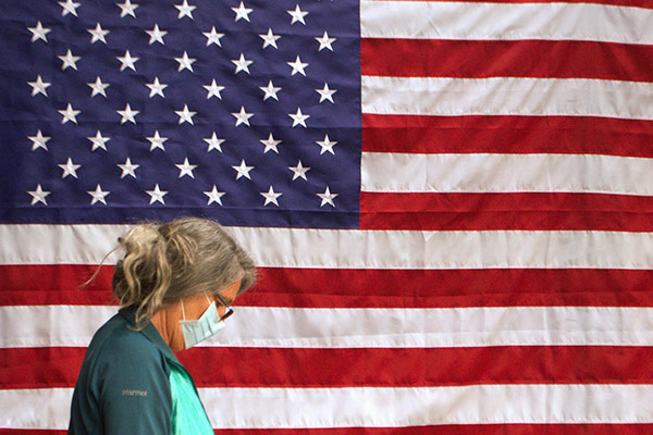 Woman wearing a face mask standing in profile in front of an American flag