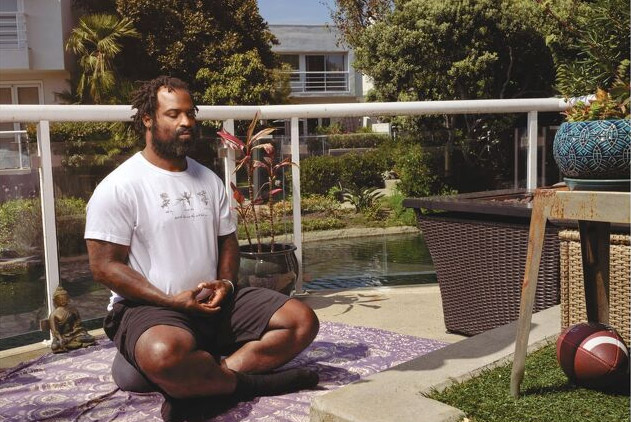 Former NFL player Ricky Williams meditates on an outdoor balcony.