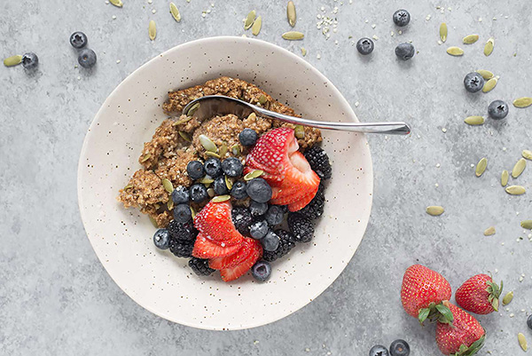 A bowl of healthy baked oatmeal with strawberries, blueberries, and blackberries