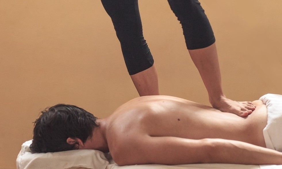 A person lying facedown receiving barefoot massage from a therapist standing over them