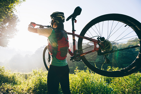 A woman facing the sun on a mountain with a mountain bike over her shoulder