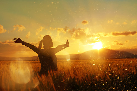Woman in field at sunset with arms outstretched