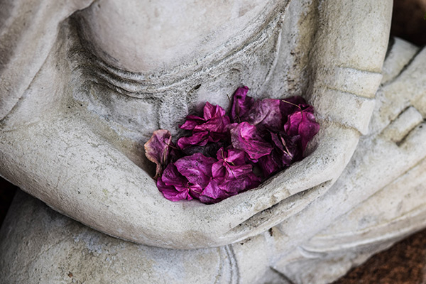 Stone Buddha statue holding dried flowers in its lap