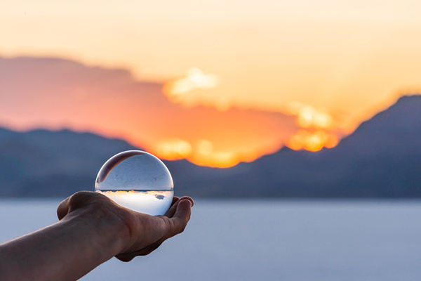colorful landscape background with hand holding crystal ball near Salt Lake City, Utah and mountain view and sunset