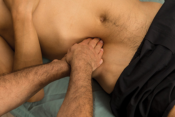 Image of massage therapist palpating the abdomen of a client, with one hand on top of the other, pressing in toward the psoas muscle
