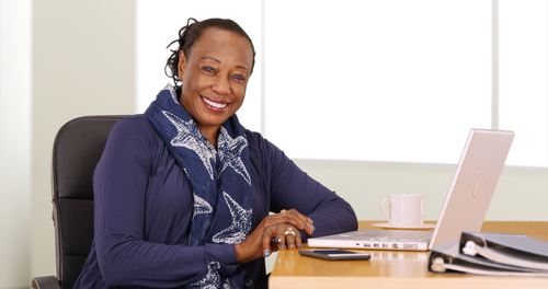 African American woman sitting at a computer smiling
