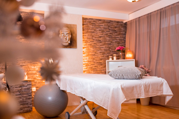 Tranquil and inviting spa setting with soft lighting and a massage table