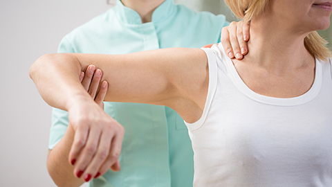 Corticobasal Syndrome--Health care worker examining woman's shoulder