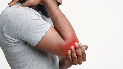 Elbow pain shown as painful red glow on a man's elbow