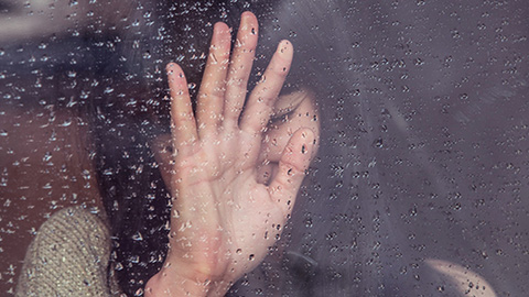A woman's hand seen through the glass of a window through the rain