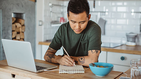 A young man sitting at a kitchen counter with an open laptop and writing in a notebook