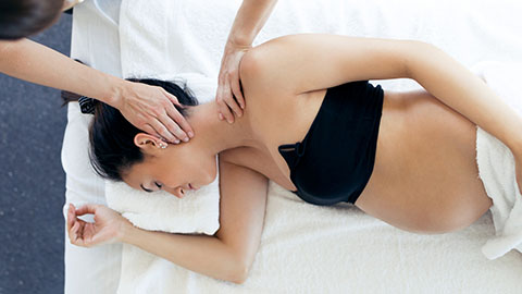 Pregnant woman lying on her side receiving a massage