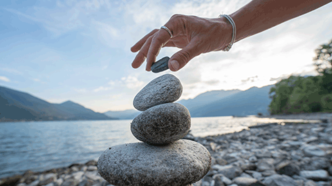 Smooth stones balanced on top of each other on a beach