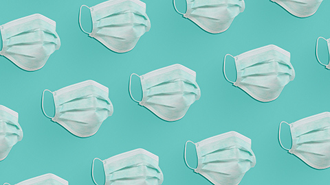 An array of surgical masks on a teal background